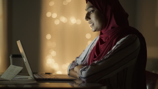 tilt up to close up of woman wearing hijab video chatting on laptop at night / cedar hills, utah, united states - convenience stock videos & royalty-free footage
