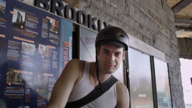tilt up to cyclist smiling at camera - fahrradhelm stock-videos und b-roll-filmmaterial