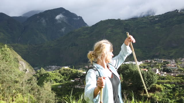 tilt up to female hiker following mountain trail, above village - kletterausrüstung stock-videos und b-roll-filmmaterial
