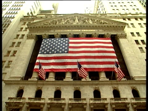 tilt up to large stars and stripes flag outside new york stock exchange - ペディメント点の映像素材/bロール