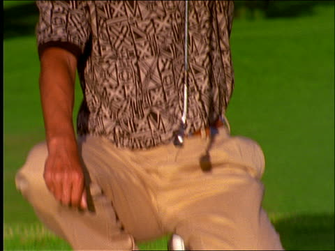 tilt up to man measuring putt on green of golf course - one mid adult man only stock videos & royalty-free footage