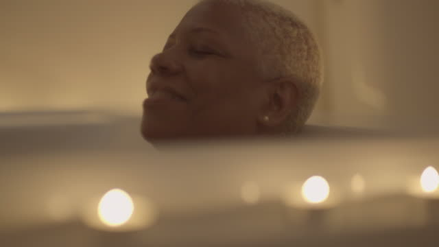 vidéos et rushes de tilt up to mature woman in bathtub - satisfaction