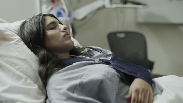 stockvideo's en b-roll-footage met tilt up to patient sleeping in hospital bed with arm in sling / salt lake city, utah, united states - menselijke arm