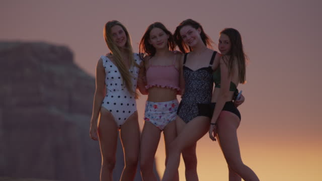 tilt up to portrait of girls wearing bathing suits near rock formation at dusk / glen canyon national park, utah, united states - dreiviertelansicht stock-videos und b-roll-filmmaterial