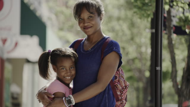 tilt up to portrait of smiling mother and daughter posing in city / provo, utah, united states - provo stock-videos und b-roll-filmmaterial