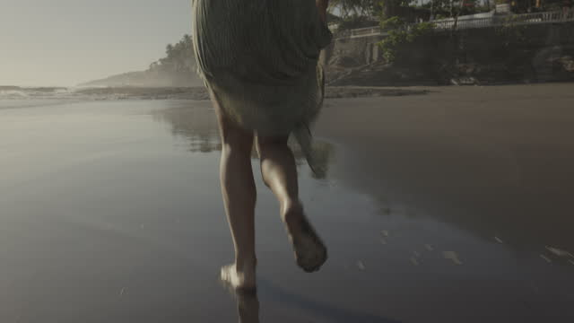 tilt up to rear view of woman in dress running on ocean beach / el tunco, la libertad, el salvador - differential focus stock videos & royalty-free footage