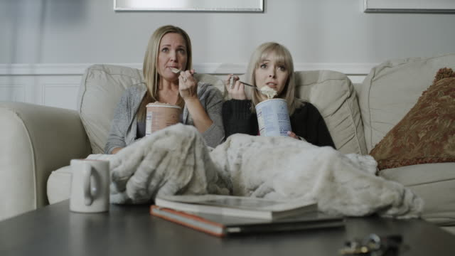 tilt up to sad women sitting on sofa eating ice cream and watching television / cedar hills, utah, united states - ice cream stock videos & royalty-free footage