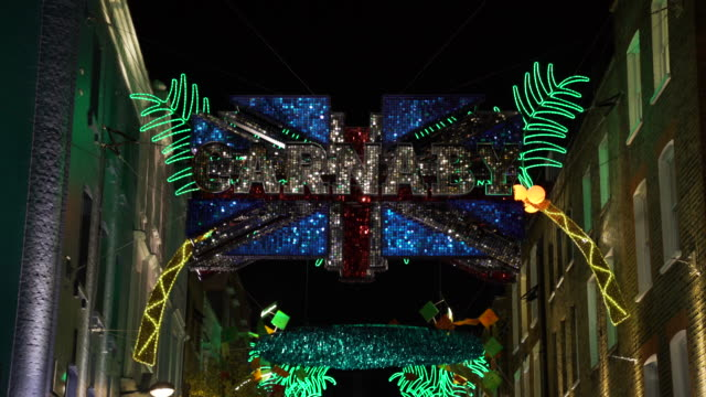 Tilt up to sequinned Carnaby Street Union Jack glittering against the night sky