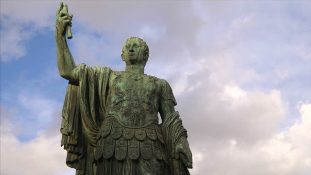 tilt up to statue of emperor julius caesar along via dei fori imperiali at the roman forum in rome, italy - statue stock videos & royalty-free footage