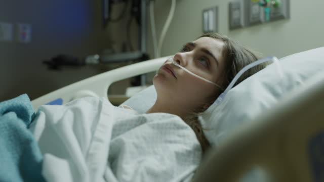 vídeos de stock, filmes e b-roll de tilt up to unhappy teenage girl laying in hospital bed with breathing tubes in nose / salt lake city, utah, united states - hospital
