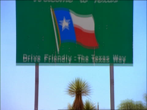 "tilt up to ""Welcome to Texas"" road sign"