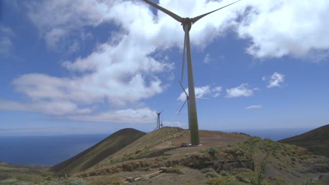 vídeos de stock, filmes e b-roll de tilt up to wind turbines slowly turning on the island of el hierro. - hierro