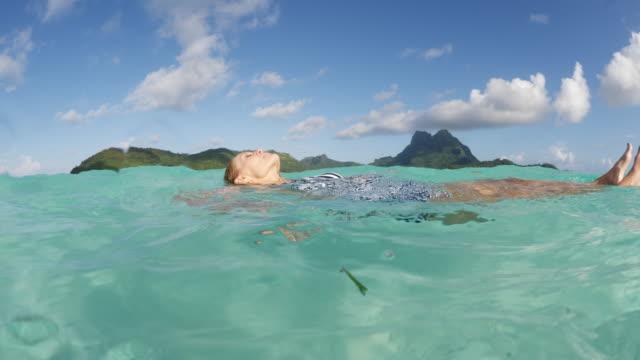 stockvideo's en b-roll-footage met tilt up to woman floating on back in ocean in tahiti / bora bora, french polynesia - menselijke rug