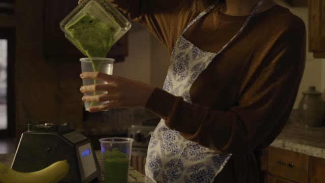 Tilt up to woman pouring smoothie into cups then leaving kitchen / Cedar Hills, Utah, United States
