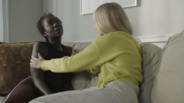 vidéos et rushes de tilt up to woman sitting on sofa comforting and hugging friend / cedar hills, utah, united states - affectueux