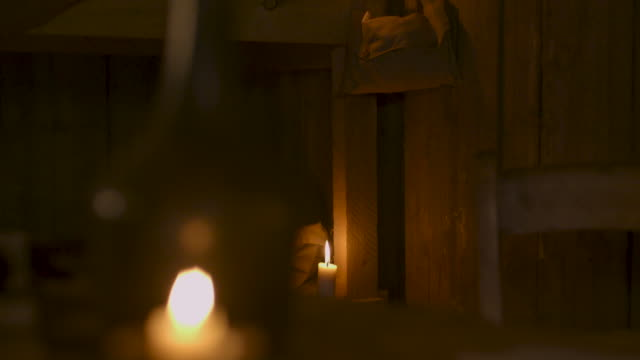 tilt up towards a shoulder bag hanging from bunks in a wwi dugout, france. - candlelight stock videos and b-roll footage