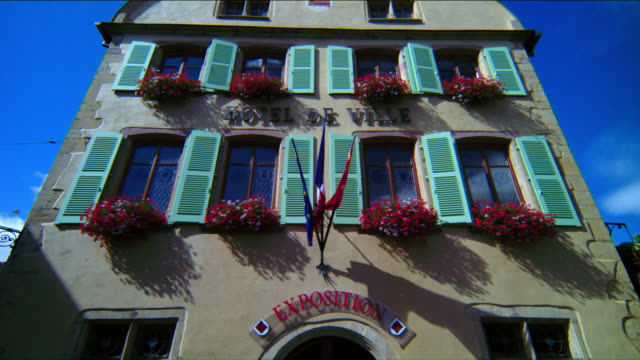 vidéos et rushes de tilt up town hall with green window shutters and flowers - mairie
