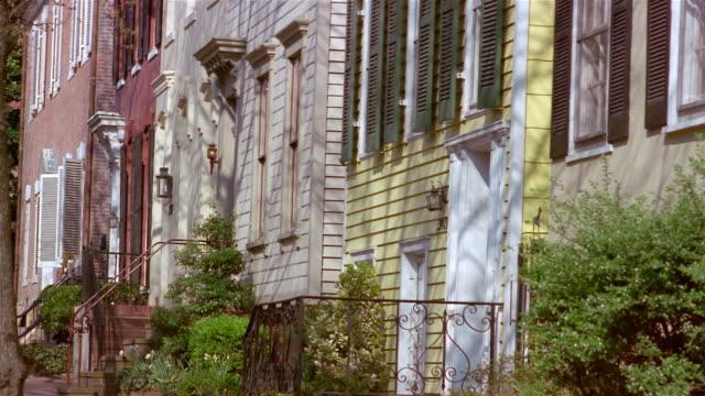 vidéos et rushes de tilt up townhouses / man walking down sidewalk / georgetown, washington, dc - georgetown washington dc