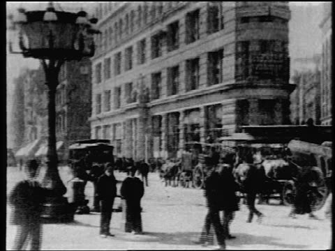 b/w 1903 tilt up trolleys + pedestrians in front of flatiron building / nyc / newsreel - anno 1903 video stock e b–roll