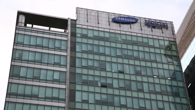 ws tilt up truck passes the cheil industries inc office building ms the logos for samsung group left and cheil industries inc are displayed atop the... - 韓国点の映像素材/bロール