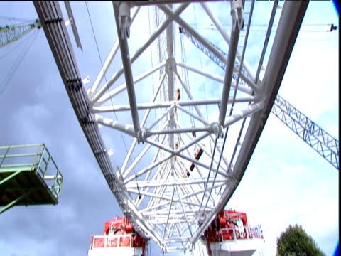 tilt up under wheel rim during construction of london eye; 1999 - erezione video stock e b–roll