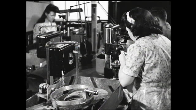tilt up view of crates full of light bulbs on the table; workers operating various machinery and testing bulbs on the assembly line - 1940 1949 stock videos & royalty-free footage