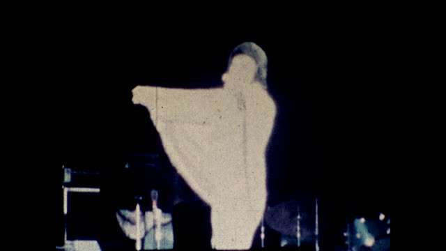 tilt up view of elvis presley performing on stage under the spotlight in front of guitarists and background singers; elvis spread out his wing-like... - las vegas stock videos & royalty-free footage