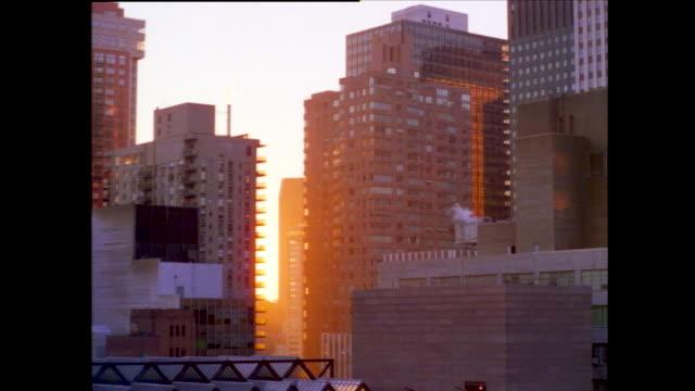 tilt up view of office buildings; moon rising next to high rise glass building; tudor city apartment with smoke; sunset through the manhattan skyline - world trade center manhattan video stock e b–roll