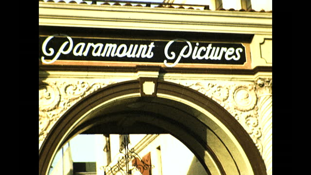 """tilt up view of people gathered in front of metal gate with sign """"paramount pictures"""", man holding pile of clothes walking out of the gate; lots of... - paramount pictures stock videos & royalty-free footage"""