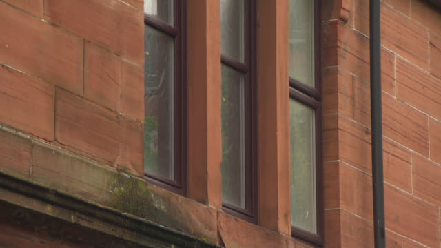 Tilt up windows and moss-covered ledges of a stereotypical Glasgow tenement building, Govan, Glasgow, Scotland.