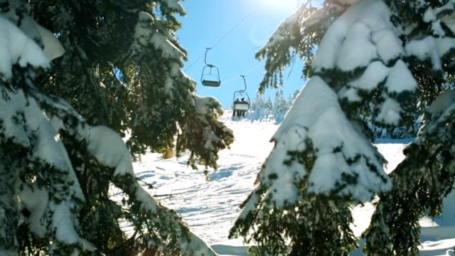 Tilt Up Winter-Szene. Sonnenstrahlen, die das Objektiv durch verschneiten Tannenzweigen zu schlagen, während der Skilift im Hintergrund passiert