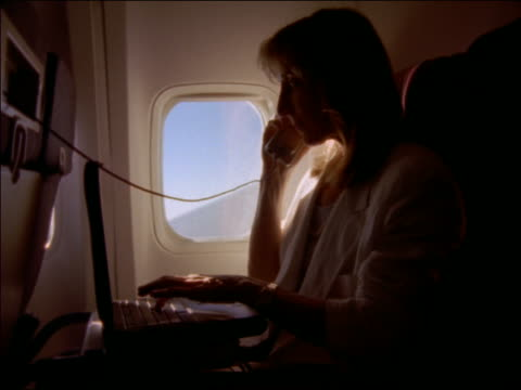 pan tilt up woman businesswoman sitting on airplane working on laptop + talking on phone - abitacolo video stock e b–roll