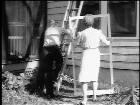 B/W 1943/44 tilt up woman holds window as man climbs ladder + grabs screen on house / Springfield, NJ