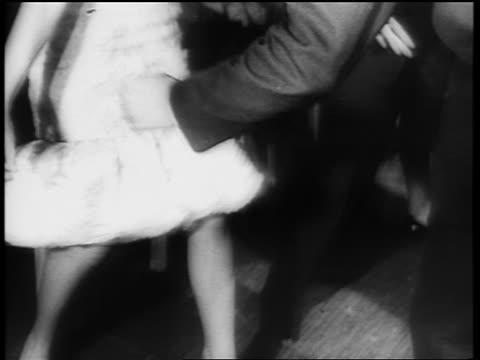 B/W 1961 tilt up woman in strapless dress dancing the Twist on dance floor / newsreel