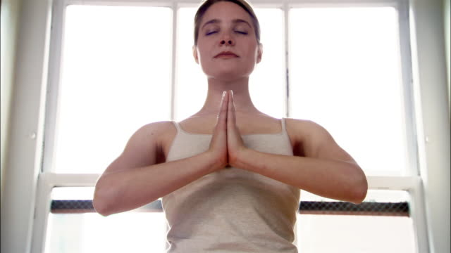 Tilt up woman standing with hands in prayer position and eyes closed in yoga studio