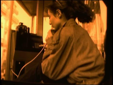 tilt up woman talking on pay phone in paris - telefonzelle stock-videos und b-roll-filmmaterial
