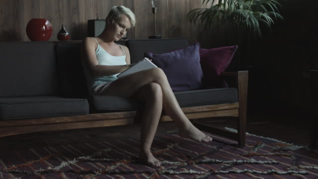 tilt up, woman uses tablet on couch - kamisol stock-videos und b-roll-filmmaterial