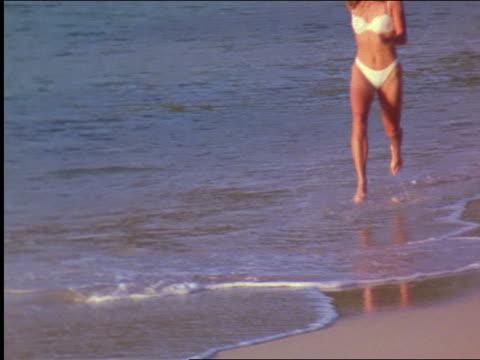 tilt up woman with yellow bikini + hat running along surf on beach / st. john, virgin islands - ワンピース型の水着点の映像素材/bロール