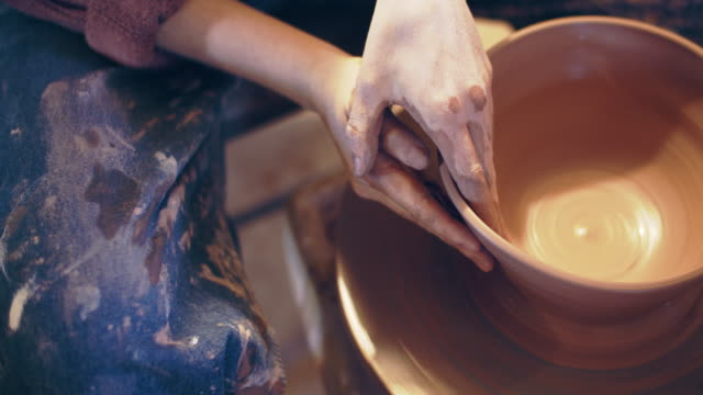 cu tilt up, women's hands shaping a bowl on a potter's wheel - 形づくる点の映像素材/bロール