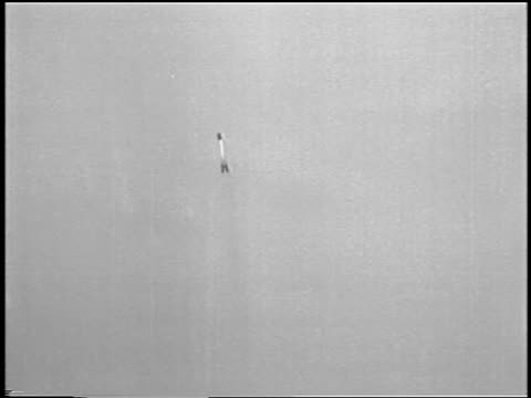 B/W 1933 tilt up world's first liquidfueled rocket launching from beach / newsreel