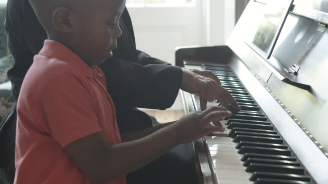 tilt up, young african american boy plays piano - ピアノ点の映像素材/bロール