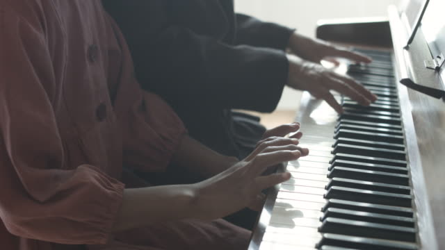 vídeos de stock e filmes b-roll de tilt up, young african american girl plays piano next to grandmother - african american ethnicity