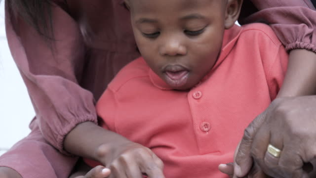 tilt up, young african american plays on digital tablet - three generation family stock videos & royalty-free footage