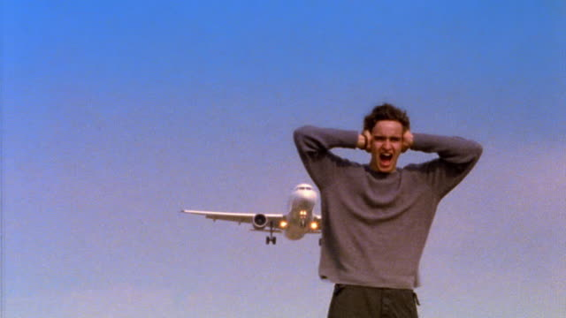 ms tilt up young man holding ears + screaming with descending airplane flying overhead / belgium - passagierflugzeug stock-videos und b-roll-filmmaterial