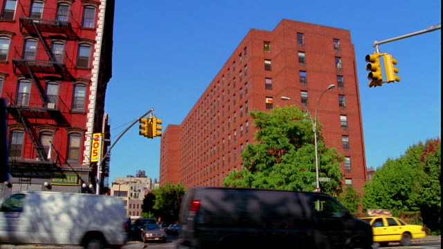 tilt up zoom in from traffic at intersection to medium shot top of apartment building / lower east side, manhattan, new york city - 2001 stock videos and b-roll footage
