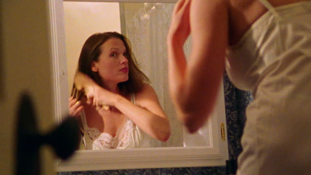CANTED tilt up zoom in reflection of woman brushing hair in mirror in bathroom