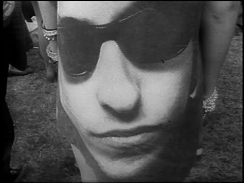 tilt up zoom out from close up of face on back of dress at be-in / hyde park, london - 1967 stock videos & royalty-free footage