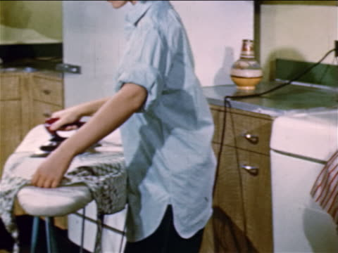 1952 tilt up zoom out pan teenage girl ironing clothes while listening to radio + talking to mother / indust. - radio stock videos & royalty-free footage