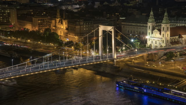 tilt view:  chain bridge with cityscape of budapest around danube river at evening from gellért hill - chain bridge suspension bridge stock videos & royalty-free footage