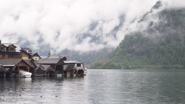 tilt view from hallstatt mountain village under bad weather condition, rain day, cloudy, austria to see traditional wood resident buildings along waterside covering rain cloud, private boat. - traditionally austrian stock videos & royalty-free footage